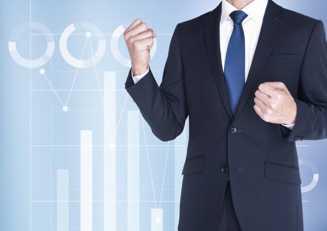 データを表す円グラフと棒グラフの背景にガッツポーズをするスーツの男性