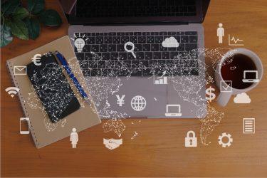 机の上に置かれたパソコンとノートと社内ヘルプデスクをイメージするアイコン