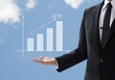上昇する棒グラフを掲げるITコンサルタント