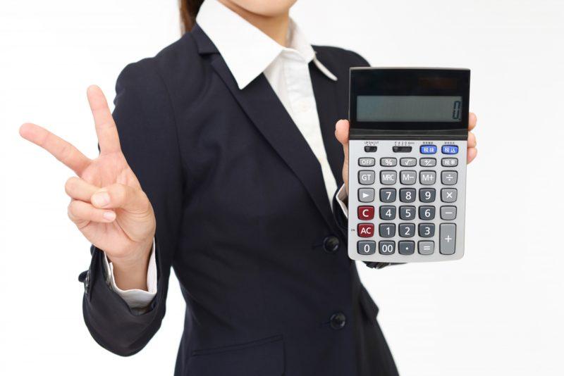 電卓を持ちながらピースをする女性