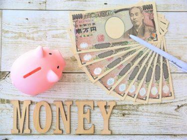 机の上に置かれた豚の貯金箱と9枚の1万円札