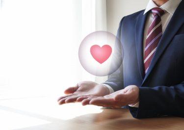 スーツの男性の手のひらに浮くハートマーク