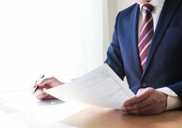 書類を持つスーツの男性