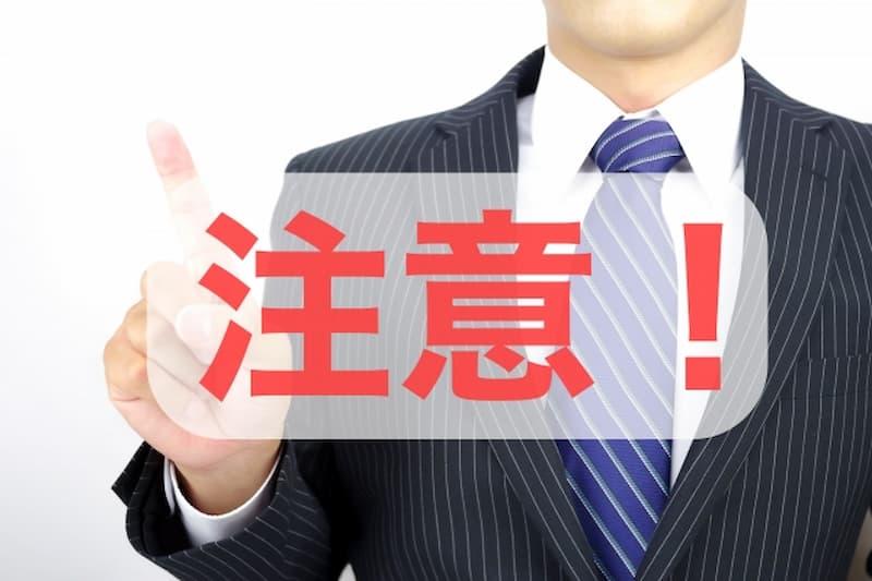 注意の文字とスーツの男性