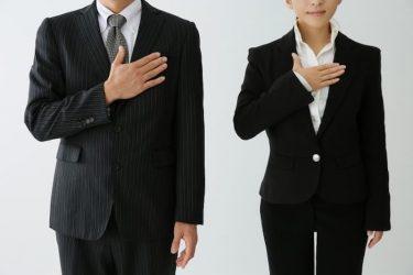 胸に手を当てるスーツの男性と女性